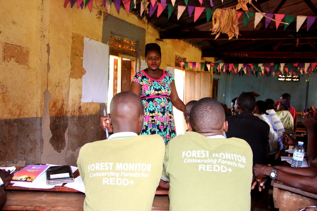 Village Enterprise Business Mentor Evelyne Kusiima poses a savings related question to Forest Monitors.