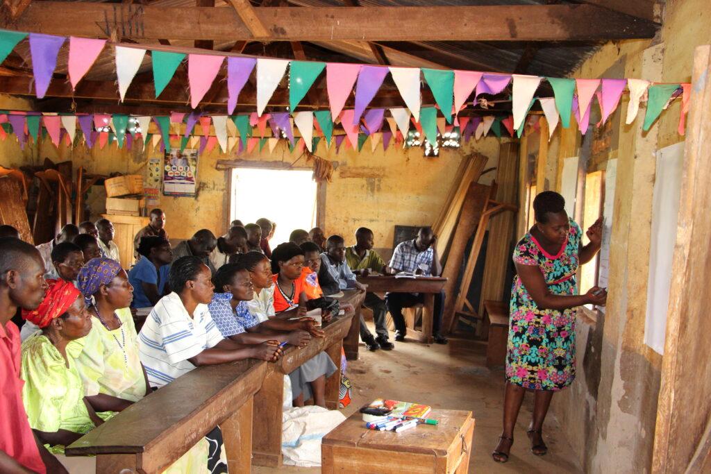 Village Enterprise Business Mentor Evelyne Kusiima leads a business savings group training for Community Based Forest Monitors in Bulimya Village, Uganda.