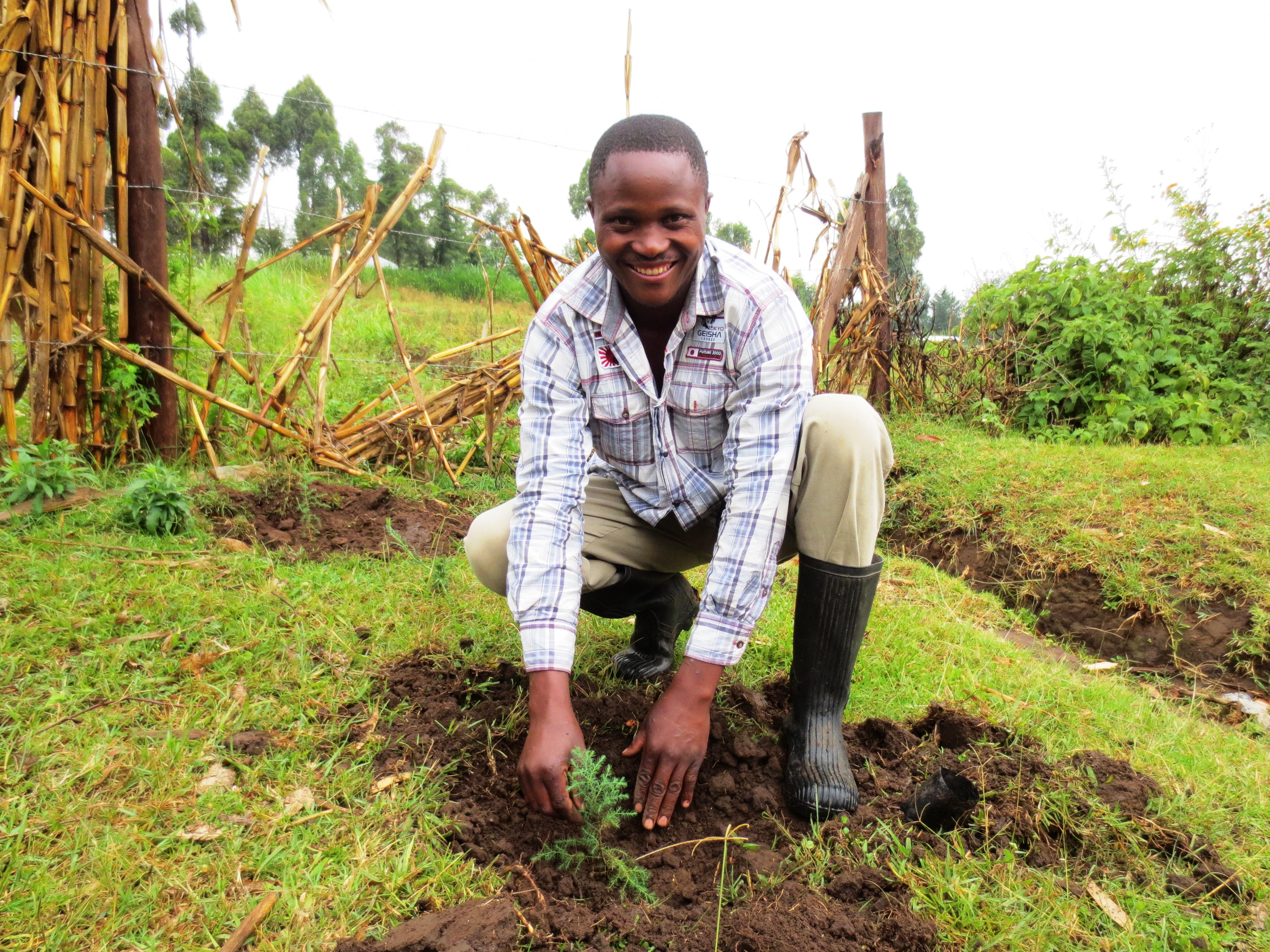 Village Enterprise Business Savings Group member Douglas Omoa plants a tree in Gidea, Kenya.