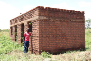 Village Enterprise business owner Moses next to a brick house