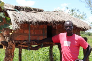 Village Enterprise business owner Moses in front of his chicken coop