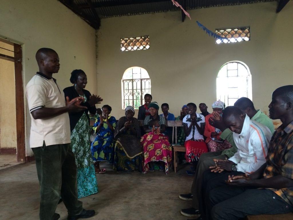 Village Enterprise Field CoordinatorSolomon Tumusiineand Uganda Country Director Winnie Auma in a Business Savings Group Meeting in Kakende
