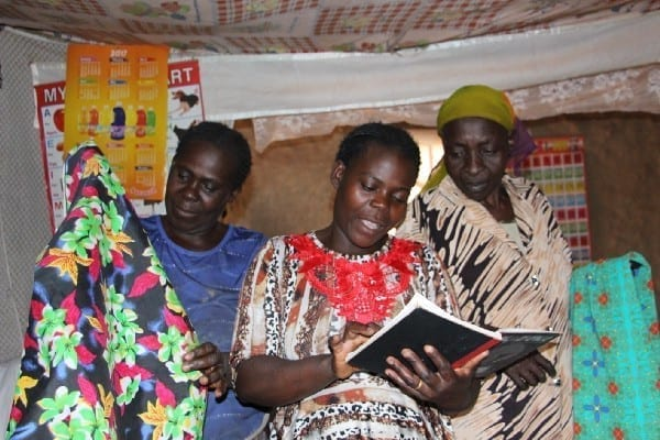Village Enterprise business owners mark down income and spending in a book