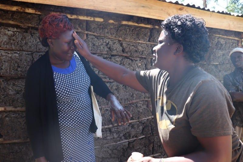 Elizabeth Kamboy applies her handmade lotion to Village Enterprise Field Associate Carolyne Wafula'sface.