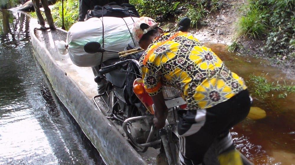 A boda (motorbike) driver loads his motorbike onto a canoe to cross ariver