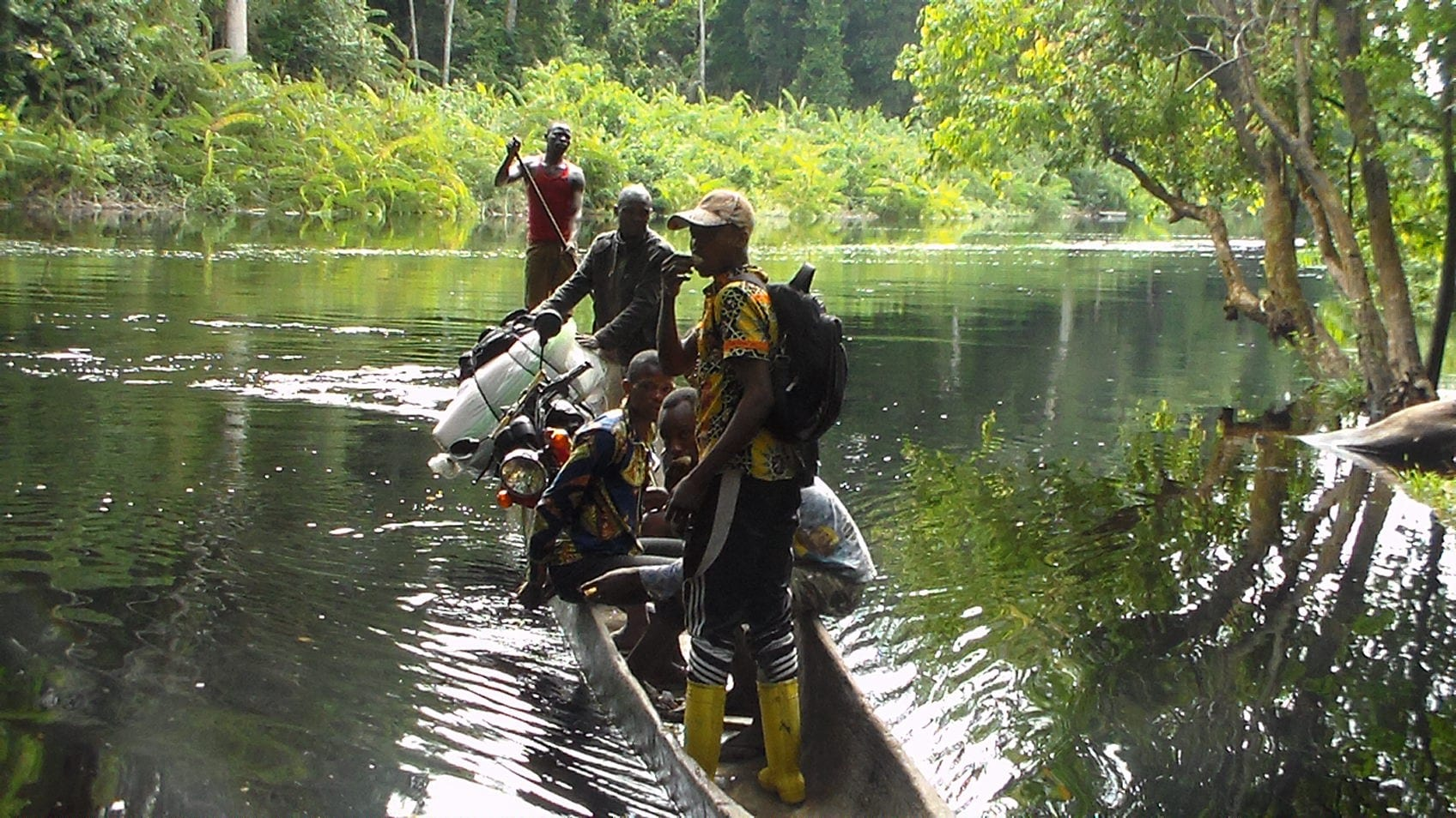 Village Enterprise staff traveling across a river in a canoe