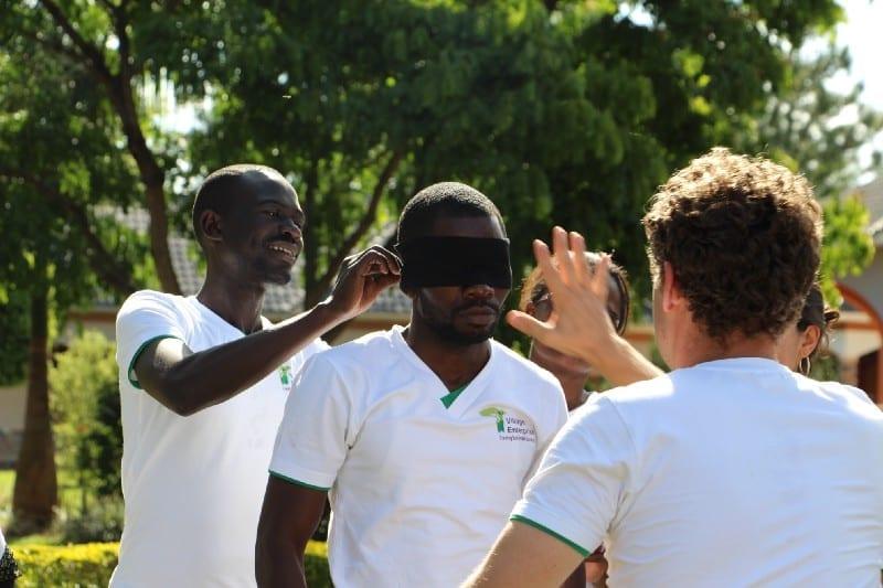 Village Enterprise staff blindfold one staff member