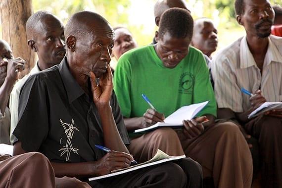 African men taking notes at Village Enterprise business training