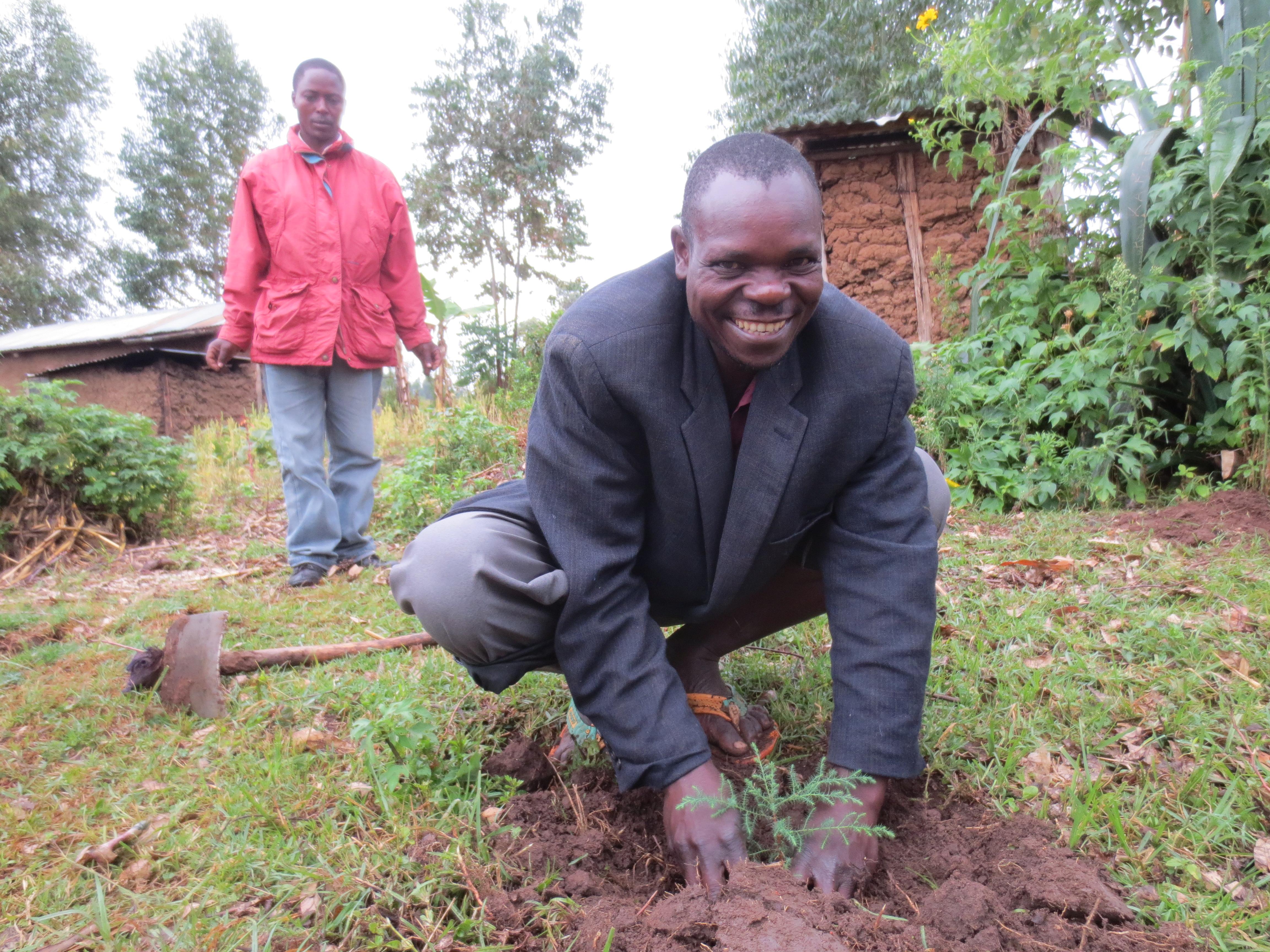Village Enterprise Business Savings Group Secretary John Mbita Smiyu plants a tree