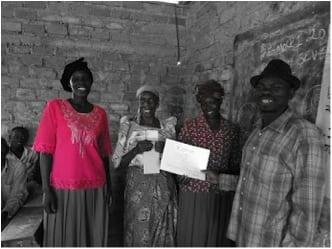 a few Village Enterprise business owners holding their graduation certificates