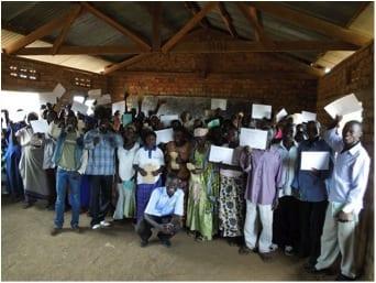 Village Enterprise business training group holding their graduation certificates