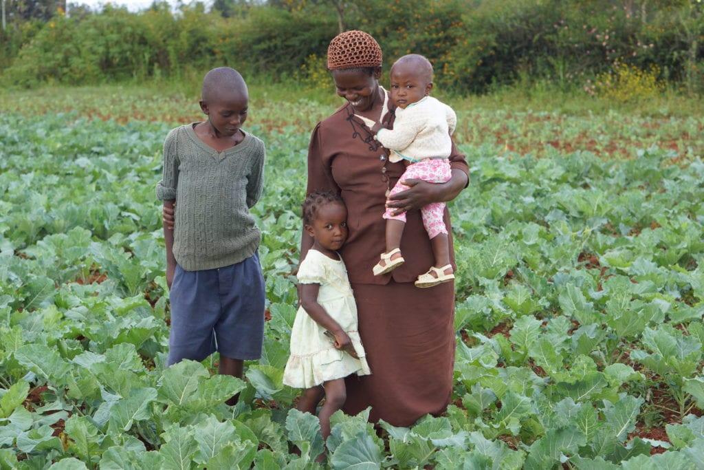 Village Enterprise business owner and her children in their fields