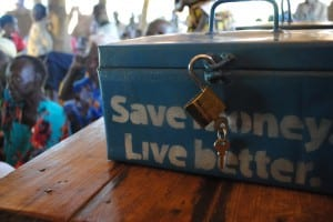 "Village Enteprise savings box labeled ""Save money, live better"""