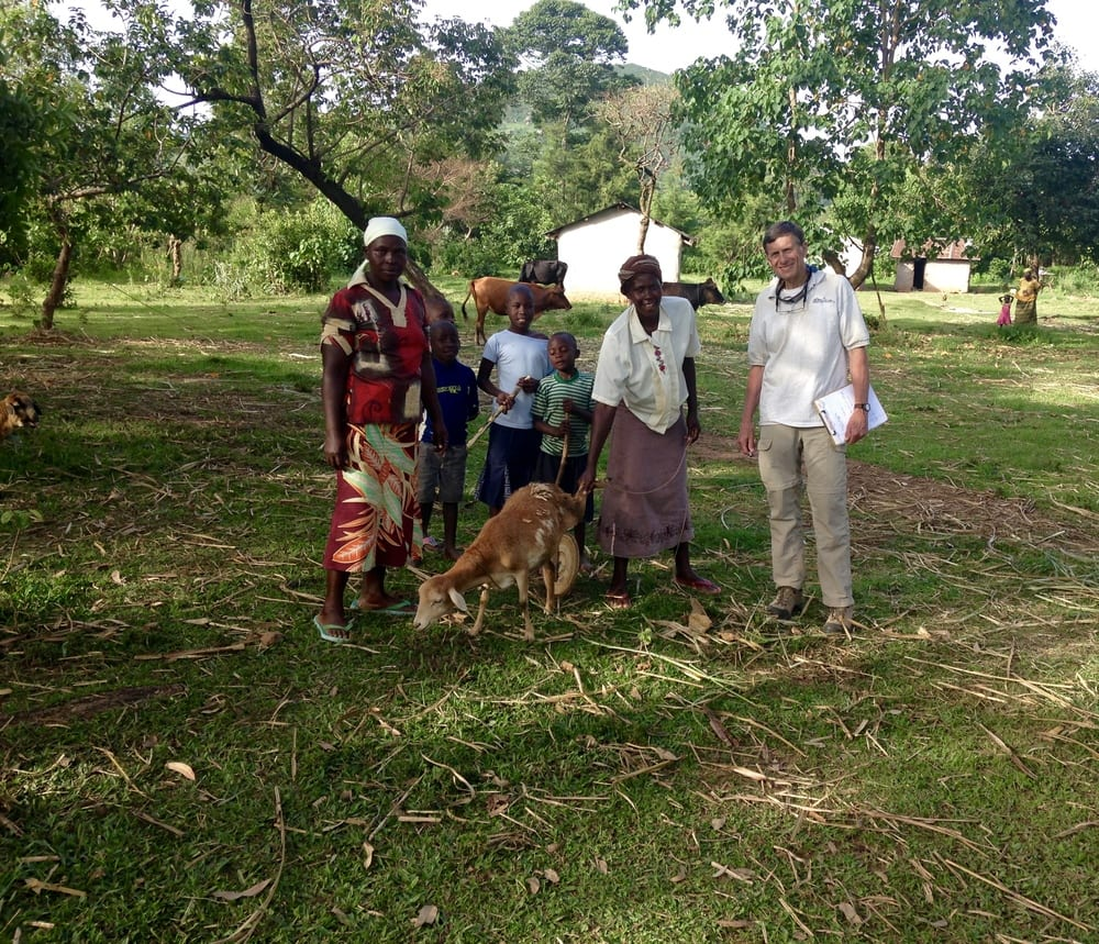 Dave Straley standing with Rebecca, her Village Enterprise business partner, neighborhood children, and the first goat