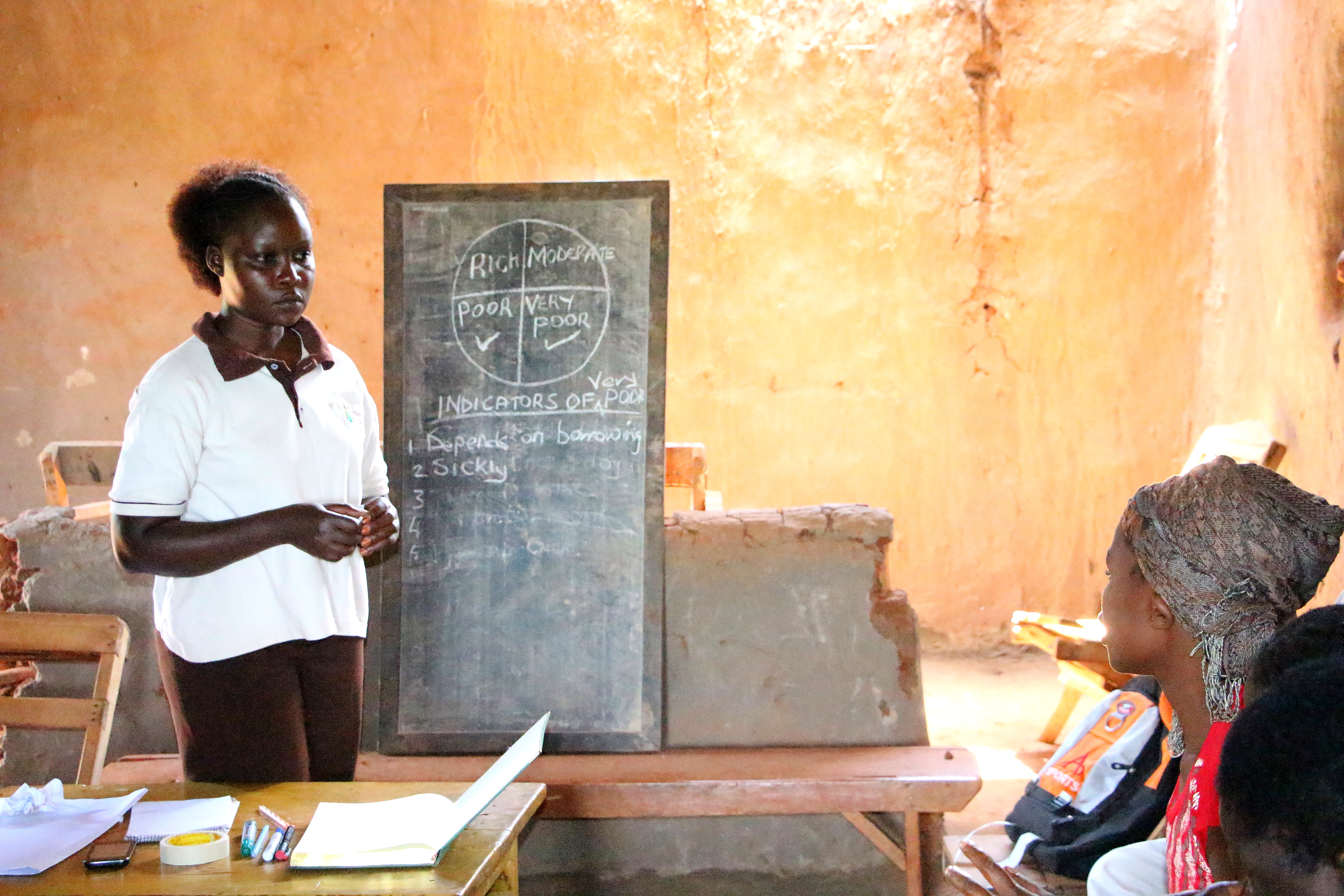 Marlene, a Village Enterprise business mentor, listens to an opinion leader explain an indicator of being very poor in Sibanga Village.