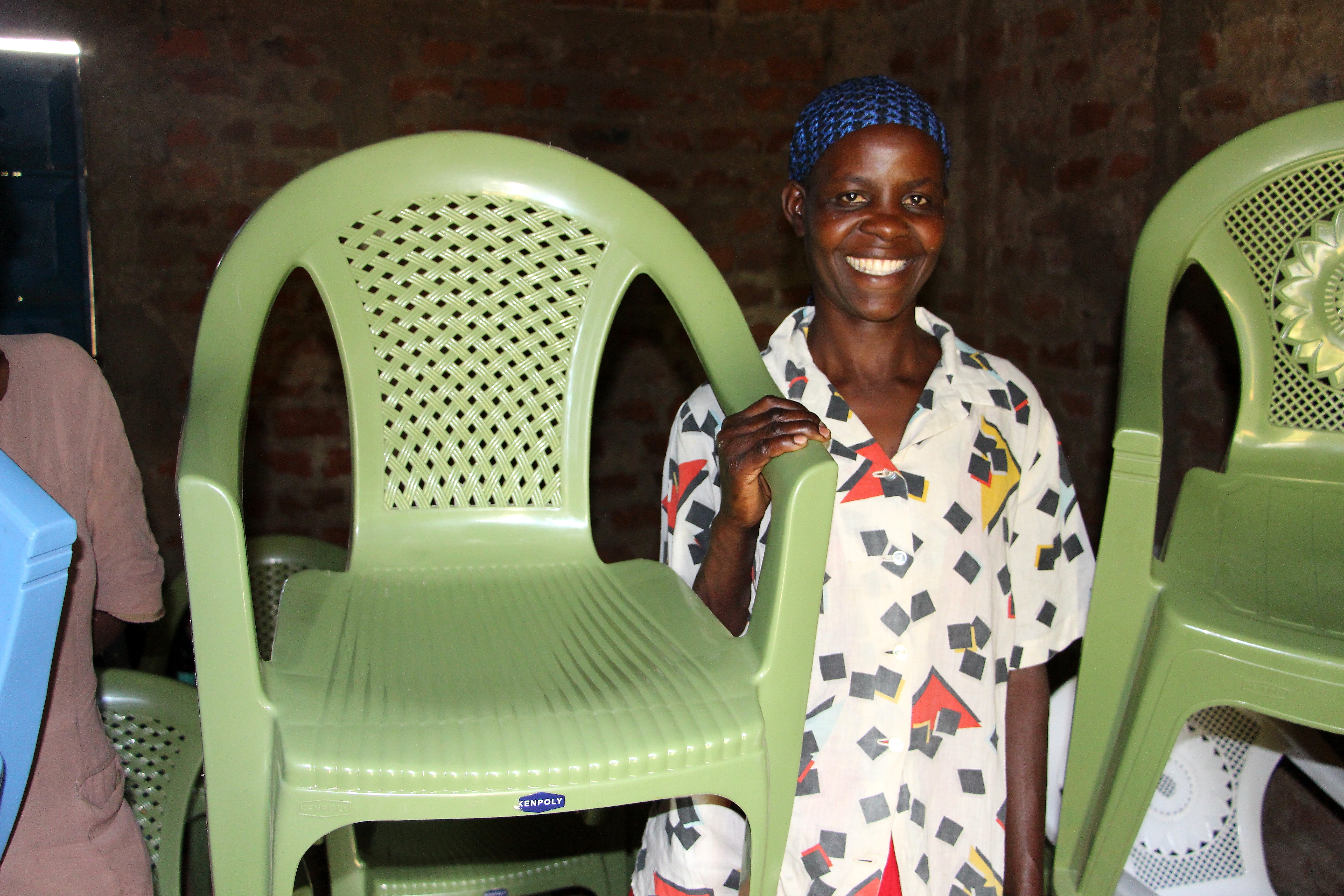 Lydya Nanjala shows off one of the plastic chairs her Village Enterprise business savings group rents out for events