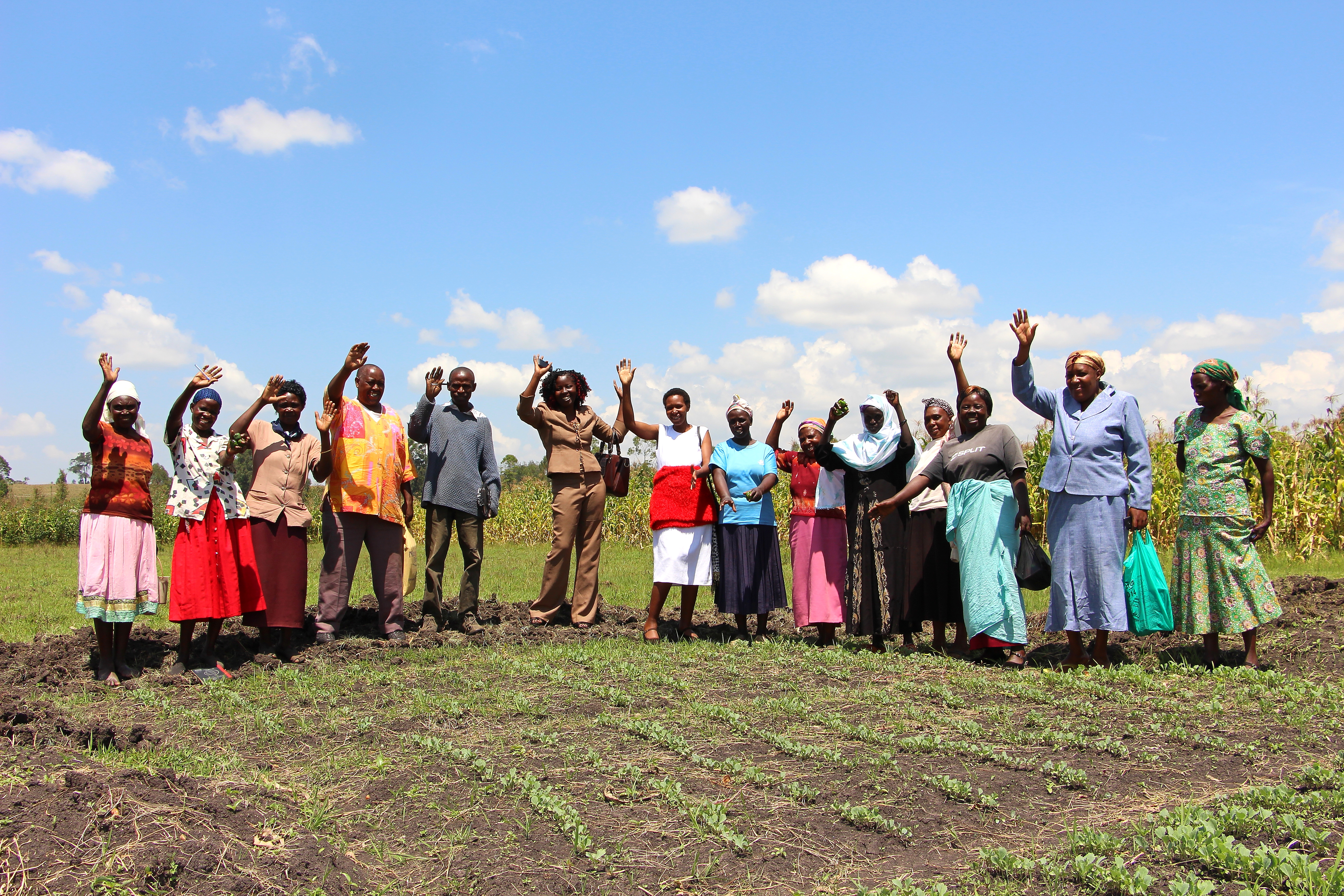 Village Enterprise Tujiinue business savings group wave next to their cabbage fields.