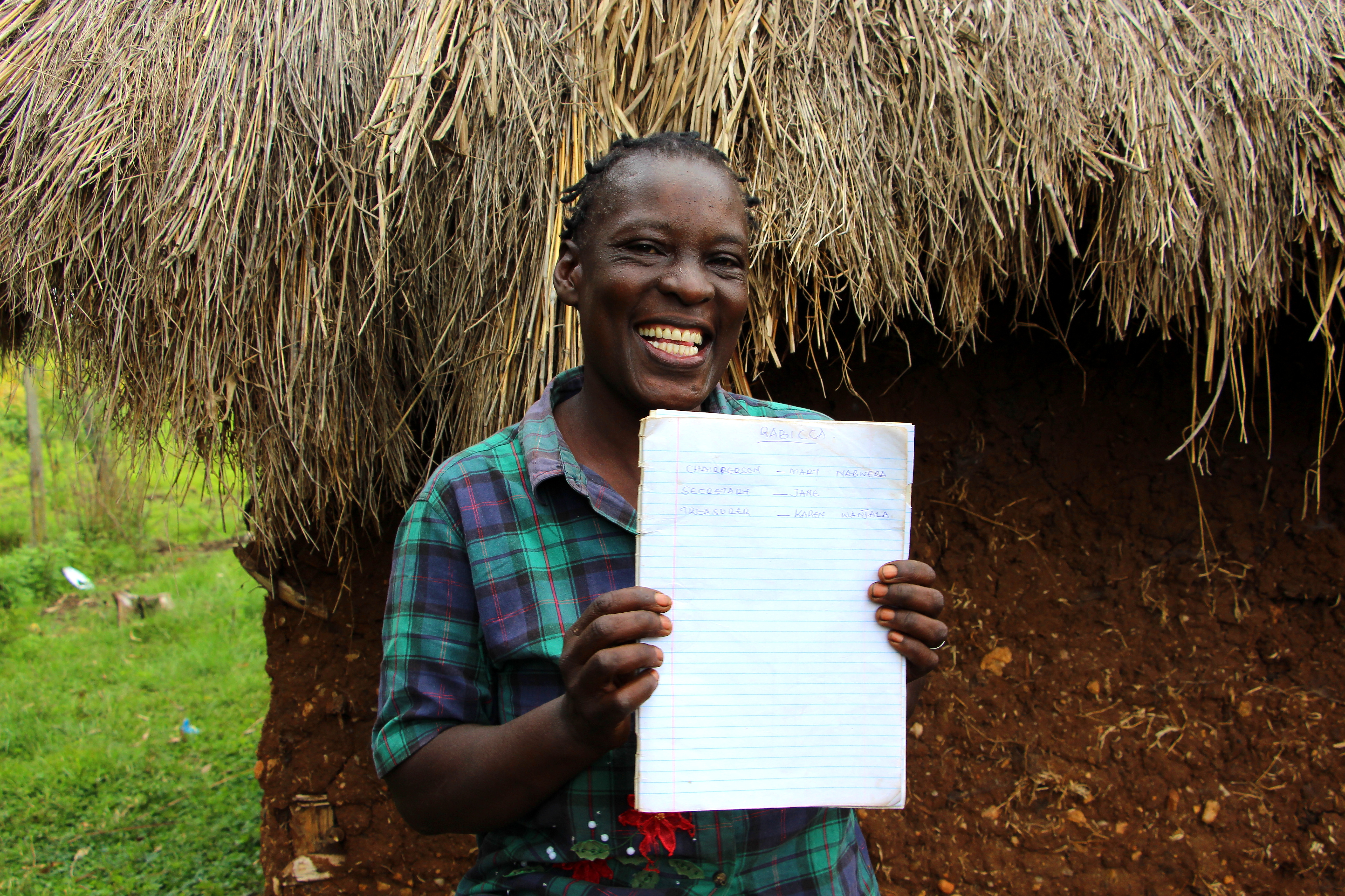 Village Enterprise business owner Mary shows her record book for her kuku (chicken) and sungura (rabbit) business.