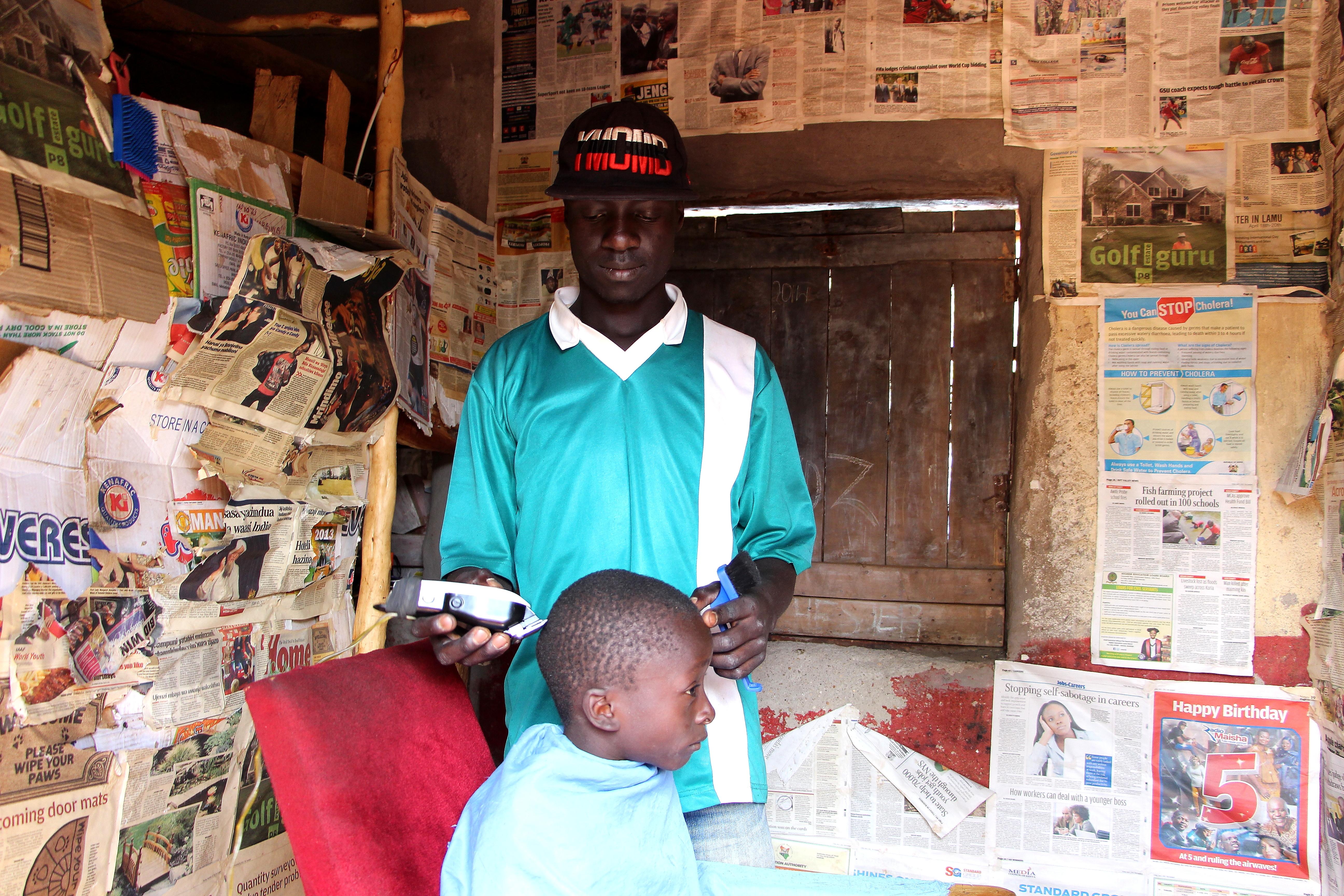 Village Enterprise business owner David Alima in his barber shop.