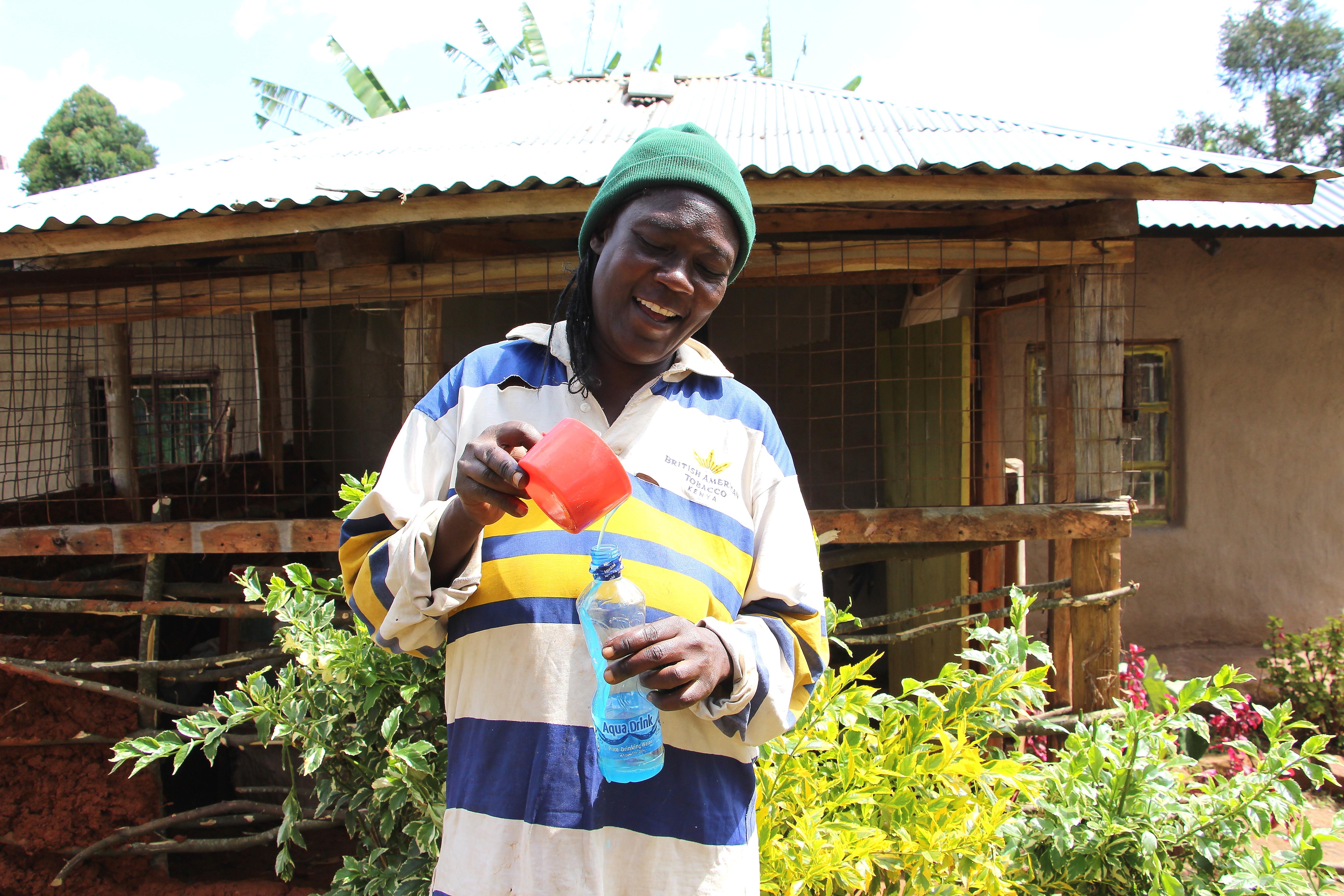 Village Enterprise business owner, Dorothy Luyai, pours liquid soap she made