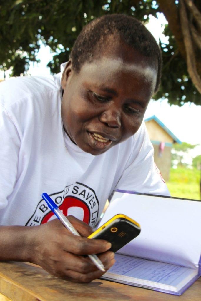 Ageyo Francis Janet tracks weekly savings for her savings group.