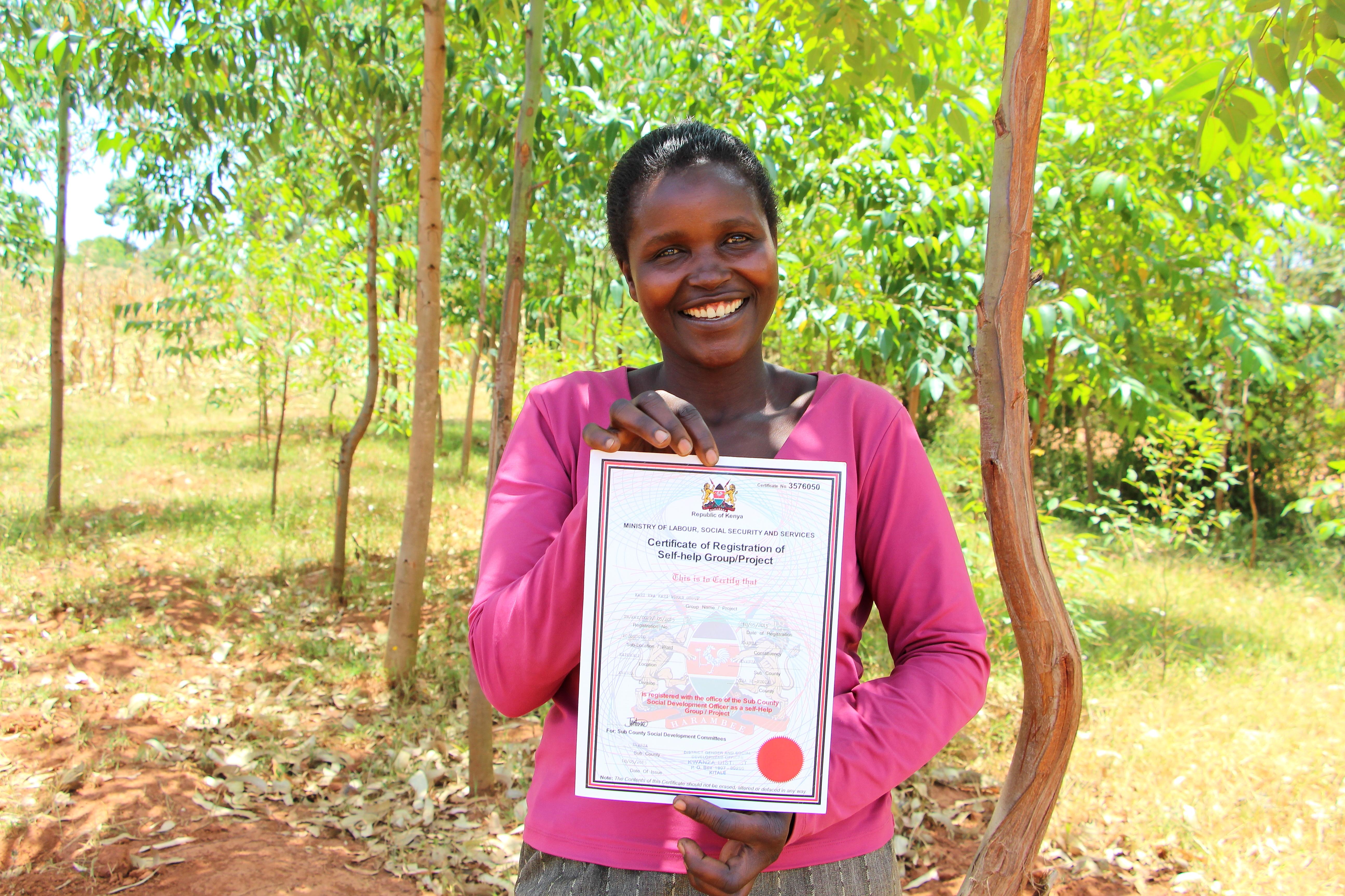 Agnes Naliaka with her Village Enterprise BSG's certificate of registration