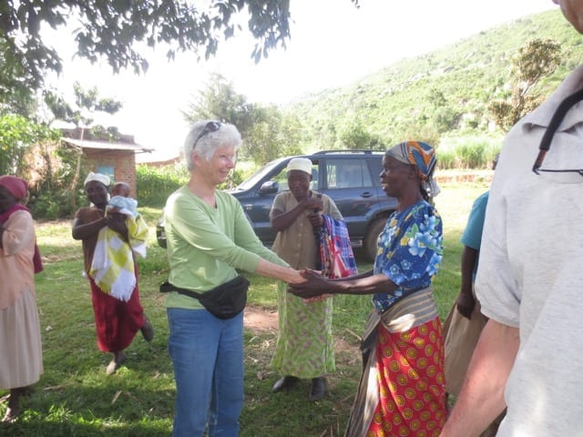 A member of 3rd Creek Foundation speaking with a Village Enterprise female business owner