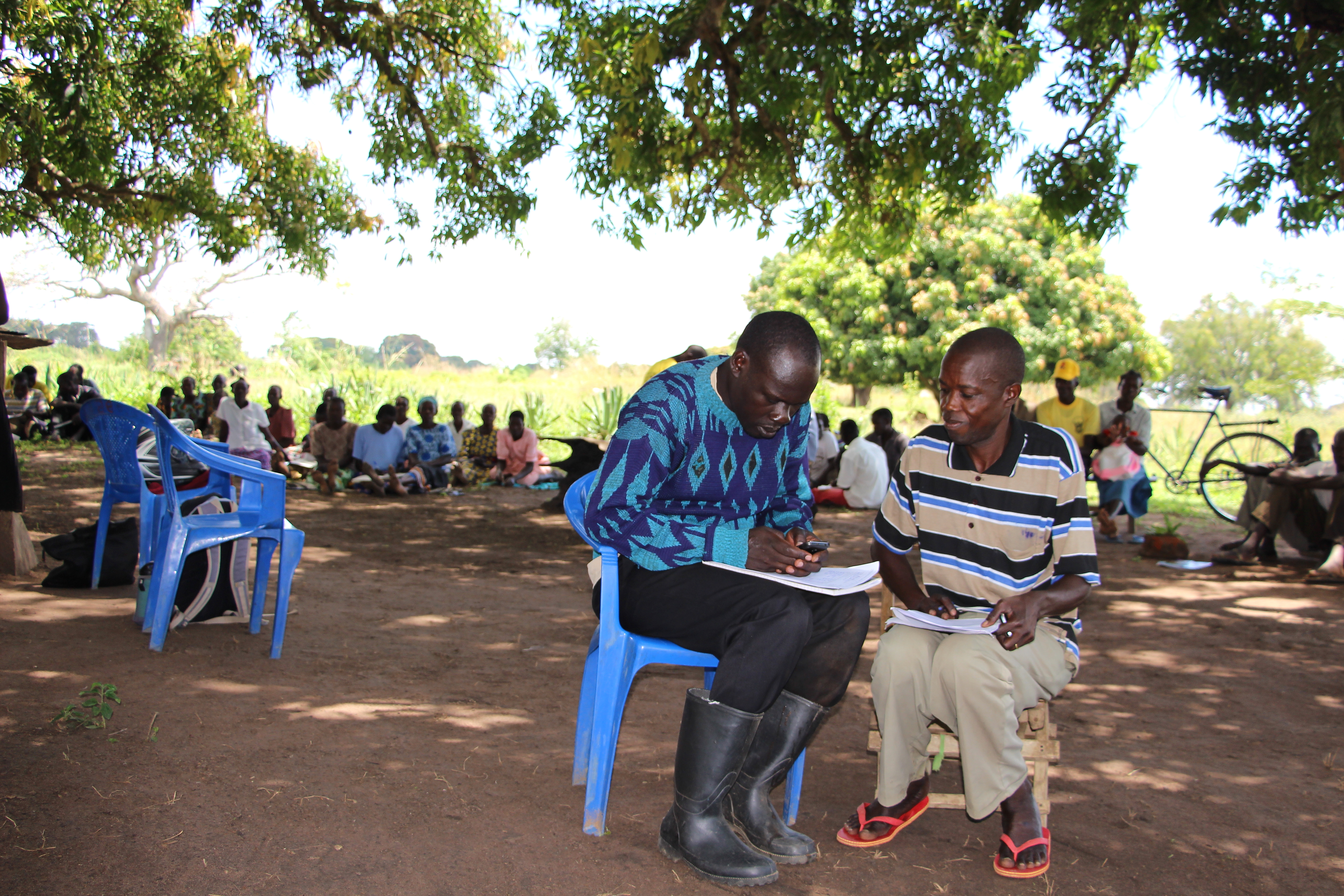 Village Enterprise Field Coordinator Maurice Eriaku works with a Business Owner to complete the Small Business Survey.
