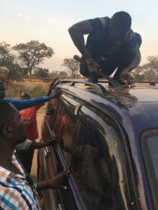Gerald Kyalisiima attempting to open a car's sun roof