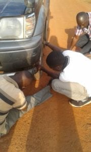 Dan Ouko, Gerald Kyalisiima, and a Good Samaritan replacing a flat tire.