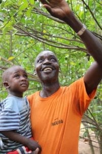 Emukajo Gilbert and his son reaching up