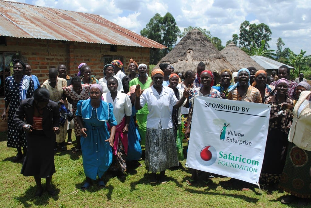 """Group of African women dancing and holding a sign reading """"sponsored by Village Enterprise and Safaricom Foundation"""""""