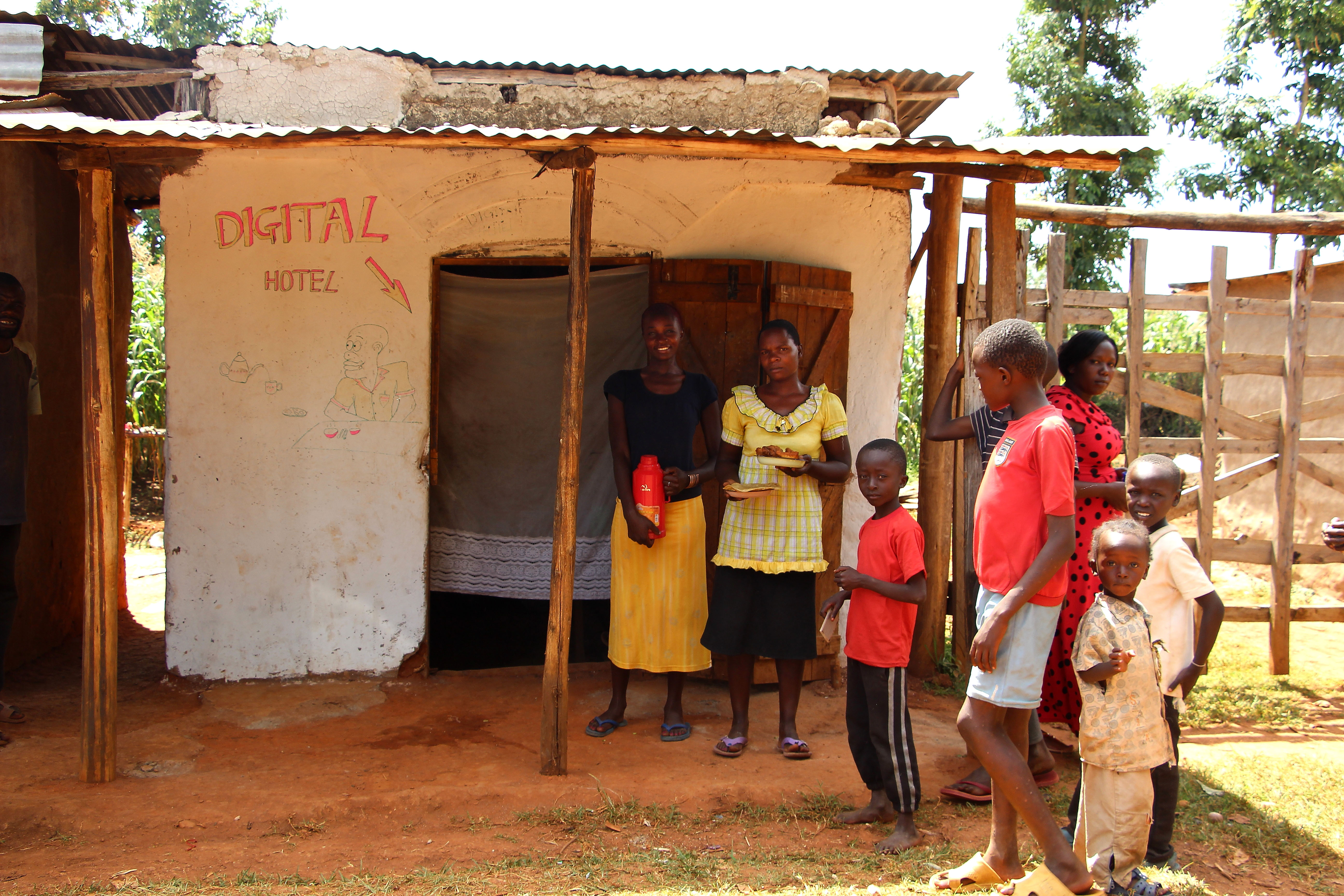 Village Enterprise business owners Esther Nekesa and Milicent Kavosa, their families, and their restaurant