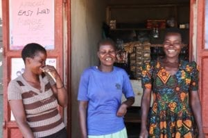 Village Enterprise business owners Jacqueline, Agens, and Irene laughing in front of their store