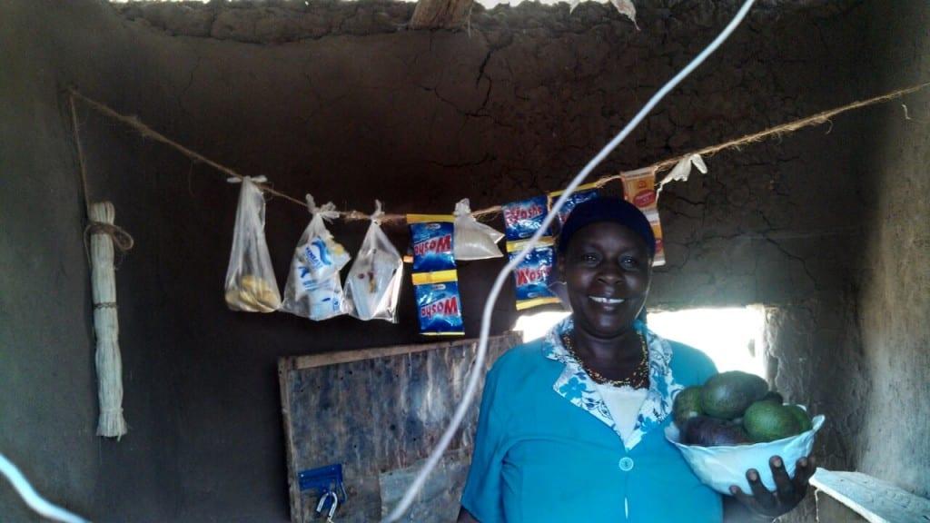 Village Enterprise business owner, Nasambu, showing a bowl of fruit