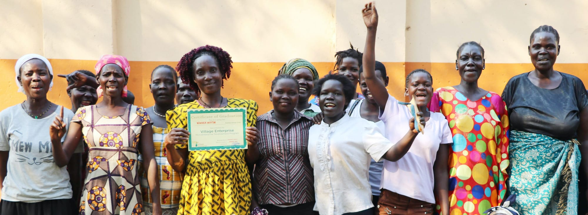 Group of women holding development program graduation certificate