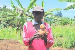 Village Enterprise business man holding potatoes