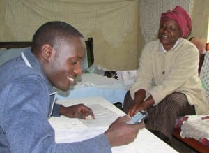 Village Enterprise business mentor checking in with a business owner