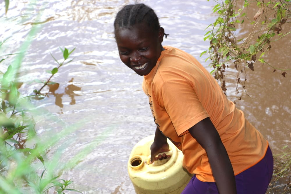 young African woman collecting water